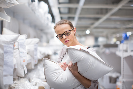Pretty, young woman choosing the right pillow for her bed in a modern home furnishings store (color toned image; shallow DOF) Stockfoto