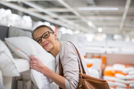 mujer en la cama: Mujer bonita, joven y elegir la almohada adecuada para su cama en una moderna tienda de muebles para el hogar (imagen a color entonado, DOF bajo)