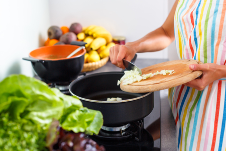 Young woman cooking in her modern kitchen (shallow DOF; color toned image)