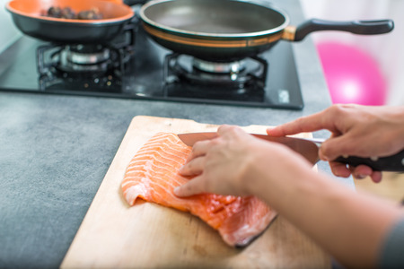 salmon filet: Young woman seasoning a salmon filet in her modern kitchen, preaparing a healthy food