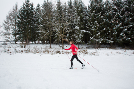 crosscountry: Cross-country skiing: young woman cross-country skiing on a  winter day (motion blurred image) Stock Photo