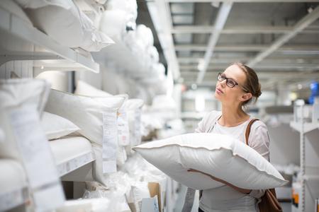 Hübsche, junge Frau, die das richtige Kissen für ihr Bett in einem modernen Einrichtungshaus wählen (Farbe getöntes Bild, flache DOF)