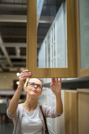 furnishings: Pretty, young woman choosing the right furniture for her apartment in a modern home furnishings store (color toned image; shallow DOF)