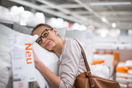 furnishings: Pretty, young woman choosing the right pillow for her bed in a modern home furnishings store (color toned image; shallow DOF) Stock Photo