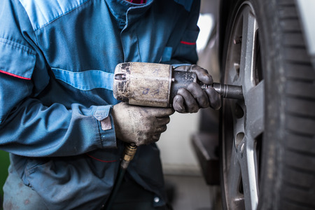 mécanicien changer une roue d'une voiture moderne (image en couleur tonique) Banque d'images