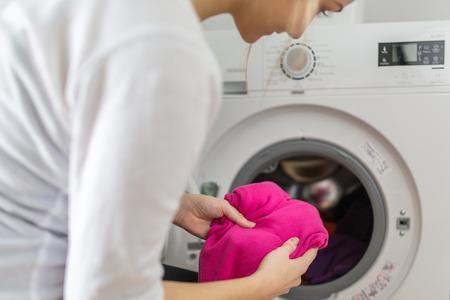 Huishoudelijk werk: jonge vrouw de was doen - brengen kleurrijke kleding in de wasmachine (ondiepe DOF, kleur getinte afbeelding)