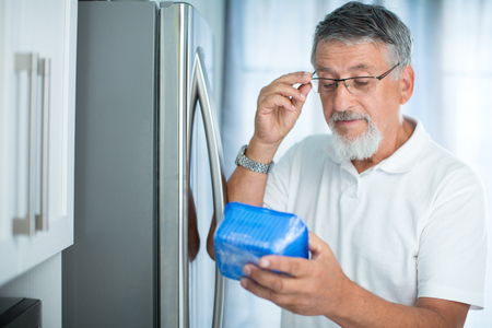 bad diet: Is this still fine? Senior man in his kitchen by the fridge, looking at the expiry date of a product she took from her fridge -