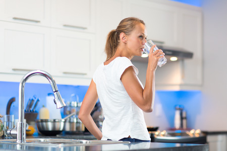 Pretty, young woman in her modern, clean and bright kitchen, pouring herself and drinking a glass of cold tap water(color toned imagey; shallow DOF)