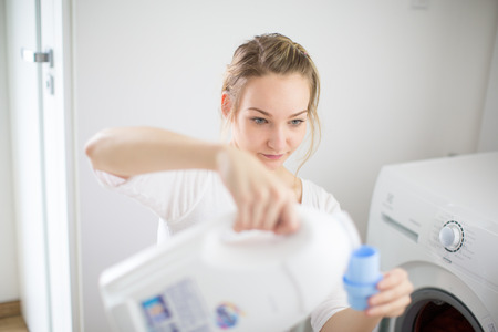 doing laundry: Housework: young woman doing laundry - putting colorful garments into the washing machine (shallow DOF; color toned image) Stock Photo
