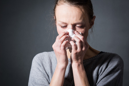 Young woman suffering from severe depressionanxietysadness, crying, tears coming from her eyes, blowing her nose