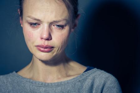 Mujer joven que sufre de severa depresión / ansiedad / tristeza, llanto, las lágrimas que viene de sus ojos Foto de archivo
