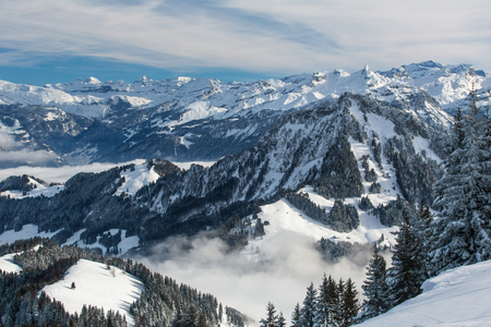 wintry landscape: Splendid winter alpine scenery with high mountains and trees covered with snow, clouds hanging low in the valley Stock Photo