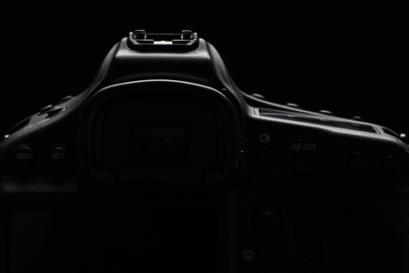 snap: Professional modern DSLR camera low key stock photoimage - Modern DSLR camera with a very wide aperture lens on with highlighted edges against black background Stock Photo