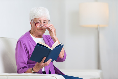 senior female: Portrait of a senior woman at home - Looking happy, looking at the camera, smiling while sitting on the sofa in her living room and reading a good book Stock Photo