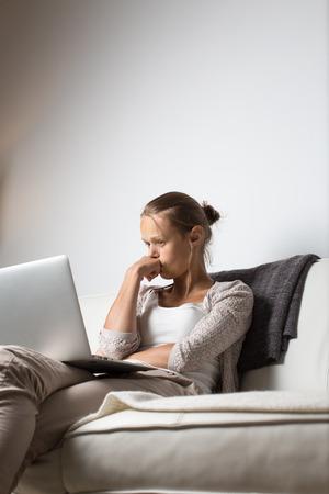 agotado: Mujer joven muy cansado, quemándose las midnigh - trabajando hasta tarde en la noche en su ordenador portátil, en casa, sentado en el sofá, frotando sus ojos cansados, tratando de mantener la concentración