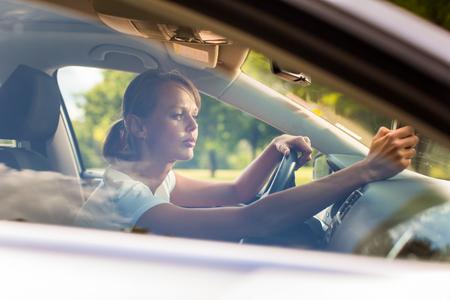 navegacion: Mujer joven que conduce su coche, de camino a casa desde el trabajo - hacer el viaje diario al trabajo Foto de archivo