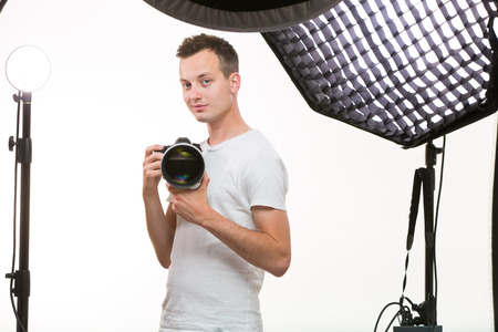 telephoto: Young pro photographer with digital camera - DSLR and a huge telephoto lens in her well equiped studio, taking photos (color toned image; shallow DOF)
