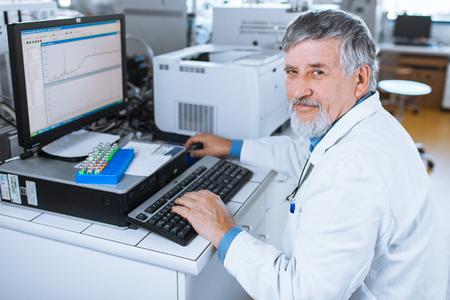 researche alto Rüsing una computadora en el laboratorio mientras trabajaba en un experimento (imagen en tonos de color) Foto de archivo