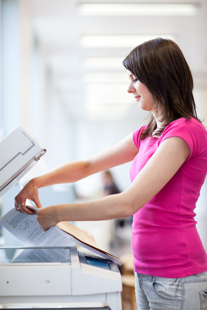 Pretty, young woman using a copy machine (shallow DOF; color toned image) photo