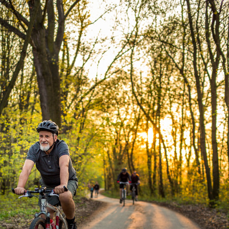 tercera edad: El hombre mayor en su bicicleta de montaña al aire libre (DOF, imagen en color entonado) Foto de archivo