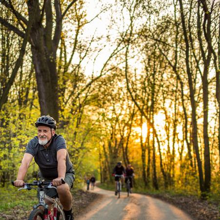 O homem sênior em sua bicicleta de montanha ao ar livre (DOF raso; imagem tonificada cor)