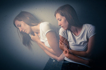 headshrinker: Young woman suffering from a severe depressionanxiety (color toned image; double exposure technique is used to convey the mood of unease, progression of the anxietydepression)