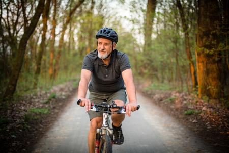Senior man op zijn mountainbike buitenshuis (ondiepe DOF, kleur getinte afbeelding)