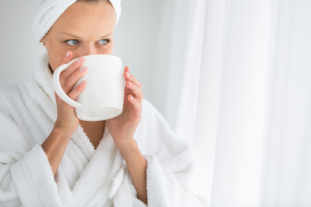sip: Gorgeous young woman wearing a bathrobe and enjoying a mug hot tea, savouring every sip (shallow DOF; color toned image) Stock Photo