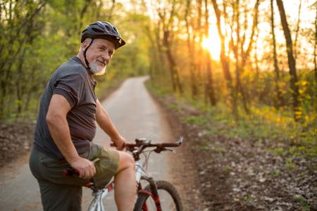 exteriores: El hombre mayor en su bicicleta de montaña al aire libre (DOF, imagen en color entonado) Foto de archivo