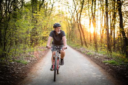 persona alegre: El hombre mayor en su bicicleta de montaña al aire libre (DOF, imagen en color entonado) Foto de archivo