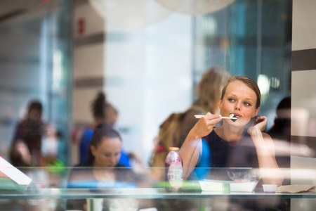 sushi: Pretty, young woman eating sushi in a restaurant, having her lunch break, enjoying the food, pausing for a while from her busy corporateoffice life