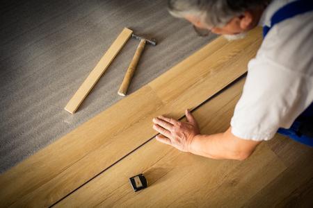 Fai da te, riparazione, costruzione e Home Concept - stretta di mano maschile che si trovano a bordo parquet / pavimenti in laminato
