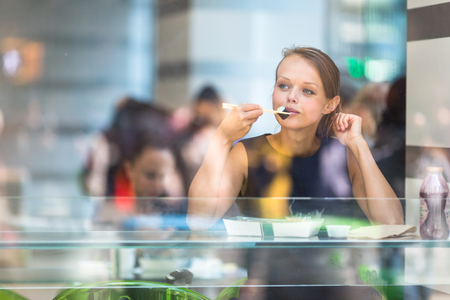 new medicine: Pretty, young woman eating sushi in a restaurant, having her lunch break, enjoying the food, pausing for a while from her busy corporateoffice life