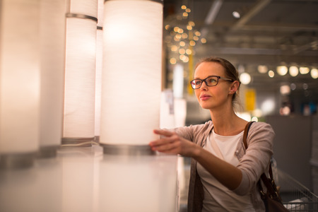 furnishings: Pretty, young woman choosing the right light for her appartment in a modern home furnishings store (color toned image; shallow DOF) Stock Photo