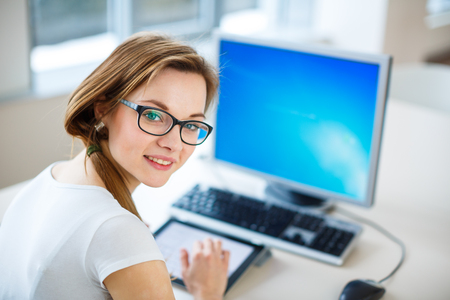Smiling female student/ businesswoman using her tablet computer and a desktop computer, staying up to date, working, looking at the camera.