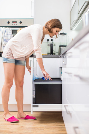 household tasks: Young woman in her lovely, modern kitchen