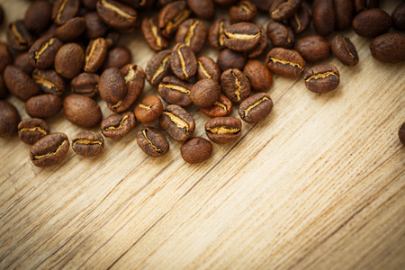 lit image: Coffee beans on a wooden desk lit by warm light (shallow DOF; color toned image)