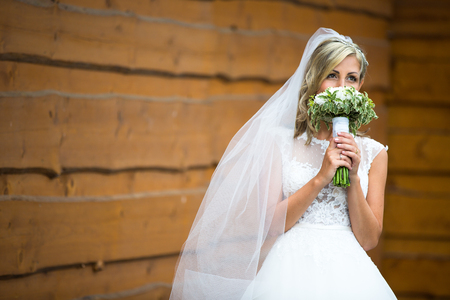 Portrait of a gorgeous young bride on her wedding day - smelling the flowers in her bouquet, enjoying the big day, feeling happy