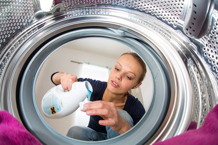 doing laundry: Housework: young woman doing laundry (shallow DOF; color toned image) Stock Photo