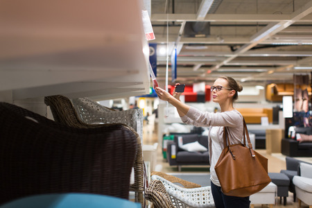 home furnishings: Pretty, young woman choosing the right furniture for her apartment in a modern home furnishings store (color toned image; shallow DOF)