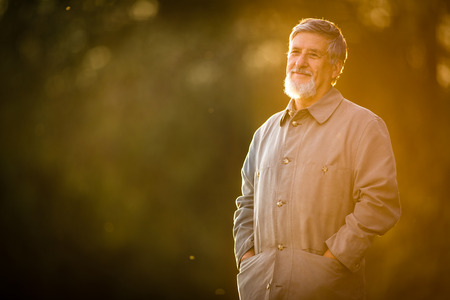 the ageing process: Portrait of a senior man outdoors, walking in a park (shallow DOF; color toned image) Stock Photo