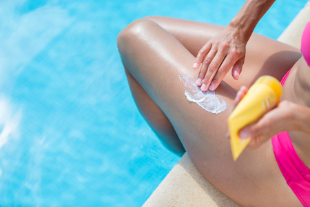 suncream: Attractive, young woman with healthy skin applying suncream by a pool (shallow DOF; color toned image) Stock Photo