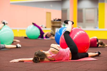Group people in a pilates class at the gym - young woman with gymball at fitness training (shallow DOF, color toned image) photo