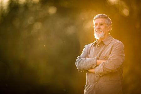 Portret van een senior man buitenshuis, wandelen in een park (ondiepe DOF, kleur getinte afbeelding)
