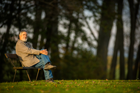 the ageing process: Portrait of a senior man outdoors, sitting on a bench in a park (shallow DOF; color toned image) Stock Photo