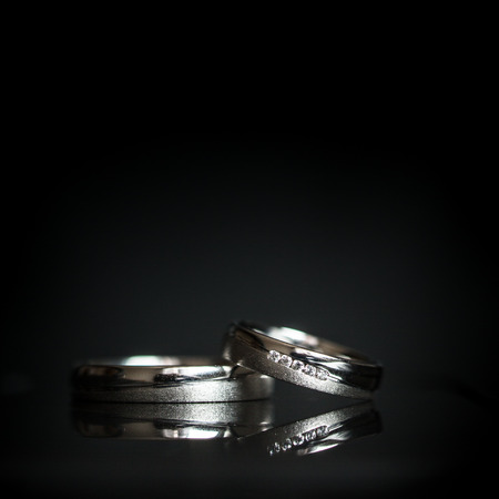 Wedding day details - two lovely golden wedding rings awaiting their moment, with some nice reflections 版權商用圖片