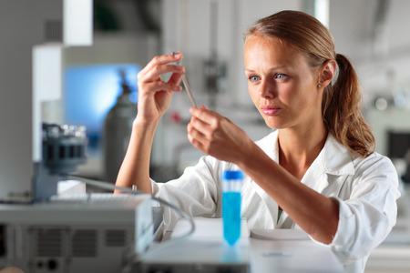investigando: Retrato de una investigadora haciendo la investigación en un laboratorio, con un tablet PC para la recogida y visualización de datos (DOF; imagen en tonos de color)