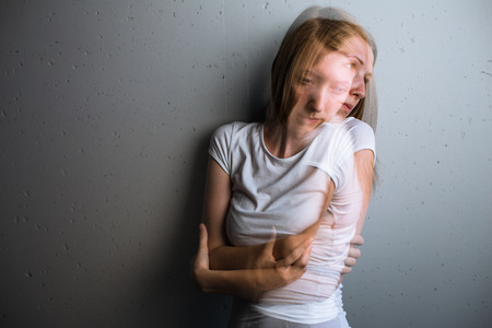 Young woman suffering from a severe depressionanxiety (color toned image; double exposure technique is used to convey the mood of unease, progression of the anxietydepression)