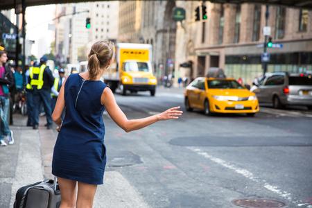 Girl calling/hailking taxi cab on Manhattan, New York City, USA