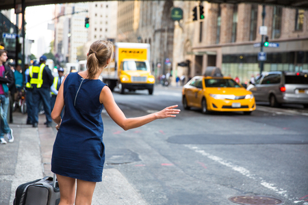 Girl callinghailking taxi cab on Manhattan, New York City, USA Stock Photo